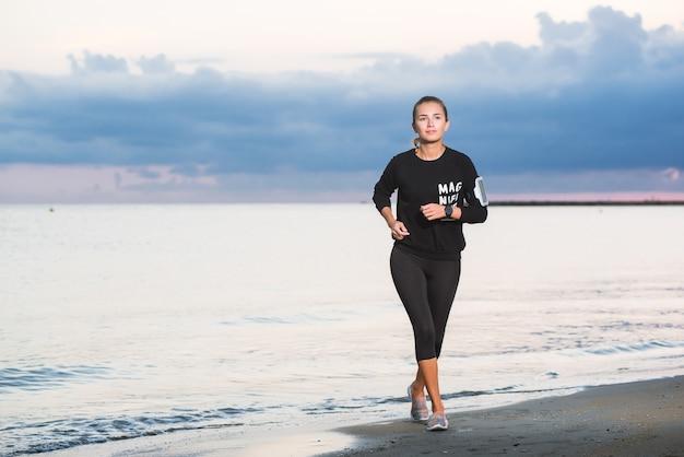 Donna che funziona sulla spiaggia all'alba