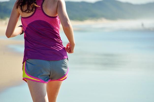 Donna che funziona sulla spiaggia, bello corridore della ragazza che pareggia all'aperto. concetto di esercizio e fitness