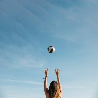 Donna che gioca a pallavolo in spiaggia