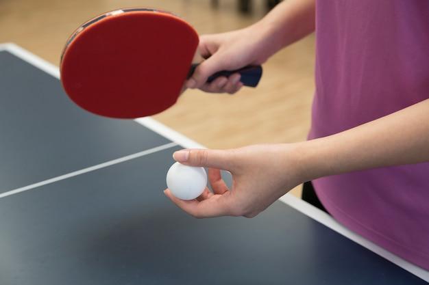 Donna che gioca a ping pong con la racchetta e pallina da ping pong in posizione di servizio