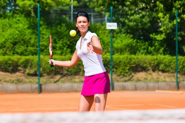 Donna che gioca a tennis sulla corte all'aperto