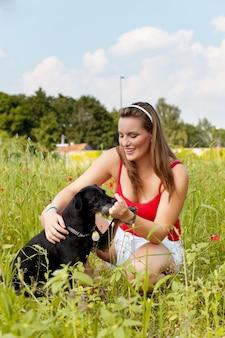 Donna che gioca con il suo cane in un prato