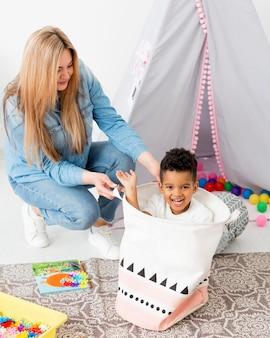 Donna che gioca con la giovane merce nel carrello del ragazzo a casa