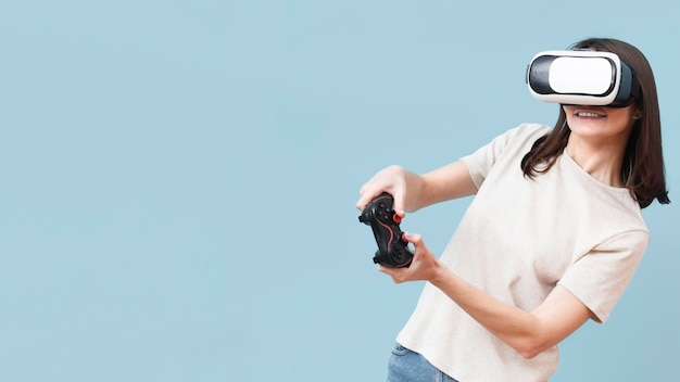 Donna che gioca con le cuffie da realtà virtuale e il telecomando