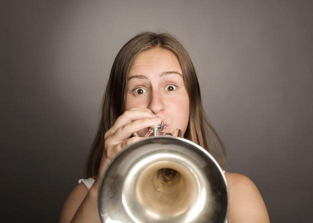 Donna che gioca tromba su gray