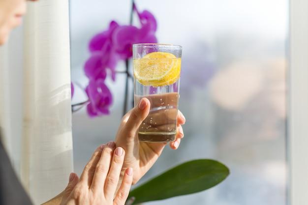 Donna che giudica di vetro con bevanda sana