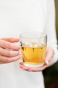Donna che giudica di vetro con tè e fiori