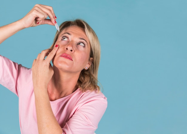 Donna che gocciola gocce mediche nei suoi occhi