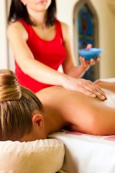 Donna che gode del massaggio nella spa benessere