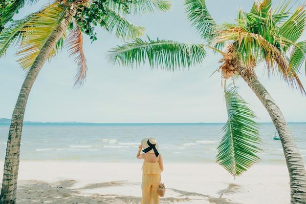 Donna che gode del rilassamento della spiaggia allegro di estate dall'acqua blu tropicale.
