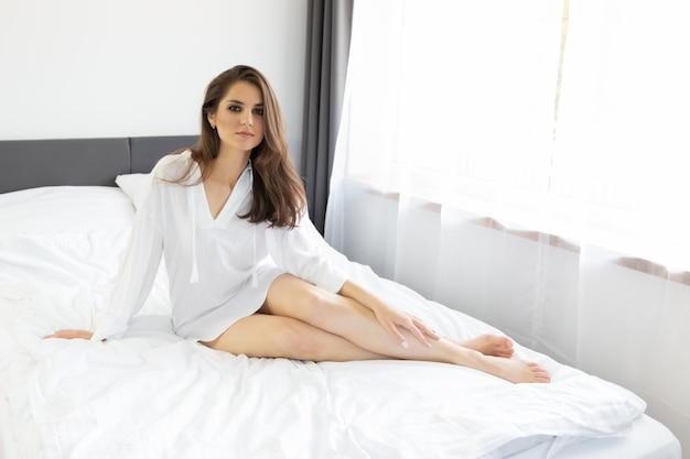 Donna che gode del risveglio mattutino in un morbido letto bianco come la neve.
