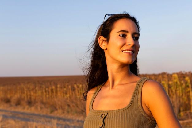 Donna che gode del sole mentre fuori nella natura