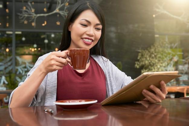Donna che gode del tempo libero al caffè