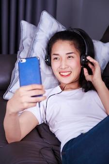 Donna che gode della musica in cuffia, rendendo selfie con cellulare mentre giaceva sul divano