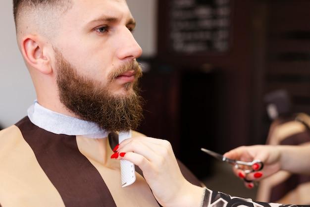 Donna che governa la barba di un cliente in un negozio di barbiere professionista