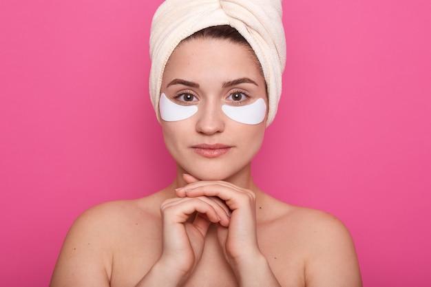 Donna che guarda direttamente la fotocamera, tenendo le braccia vicino al viso, avendo avvolto i capelli in un asciugamano