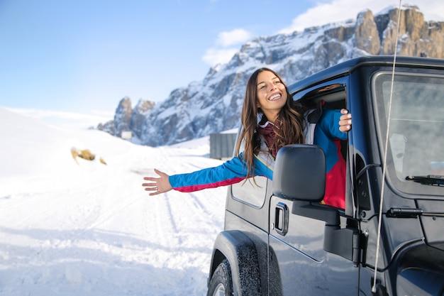 Donna che guarda fuori dal finestrino della macchina per godersi la vista della montagna