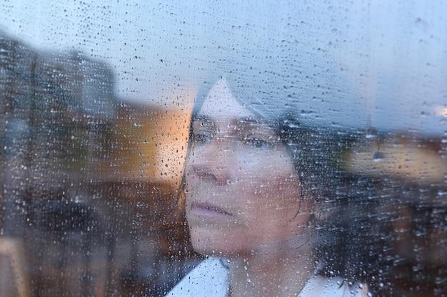 Donna che guarda fuori dalla finestra in una giornata piovosa