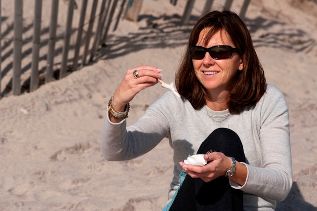 Donna che guarda i seashells sulla spiaggia negli hamptons