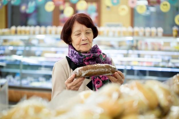 Donna che guarda il pane al negozio del supermercato