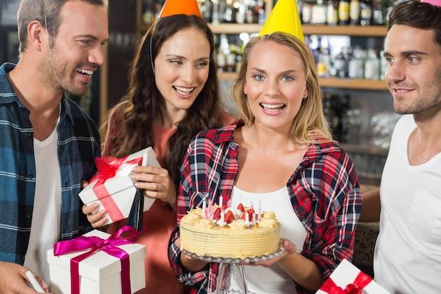 Donna che guarda l'obbiettivo con la torta in mano