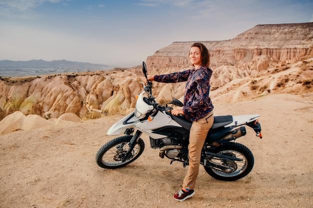 Donna che guida in moto nel paesaggio montano della cappadocia al tramonto
