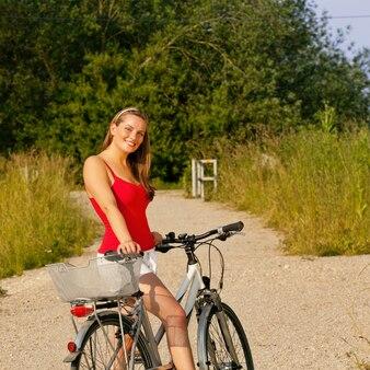 Donna che guida la sua bicicletta in estate