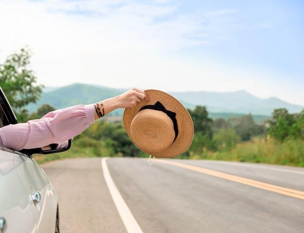 Donna che guida su strada il viaggio in auto si rilassa