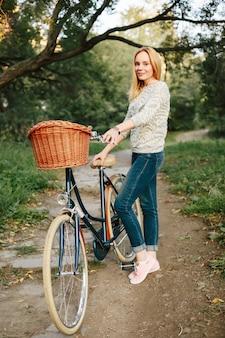 Donna che guida sulla bicicletta d'epoca con cesto