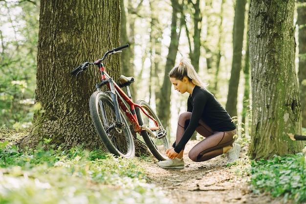 Donna che guida un mountain bike nella foresta