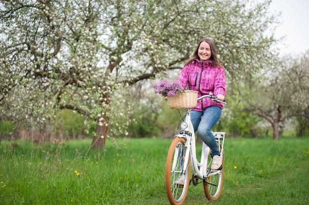 Donna che guida una bicicletta bianca d'annata con la merce nel carrello dei fiori