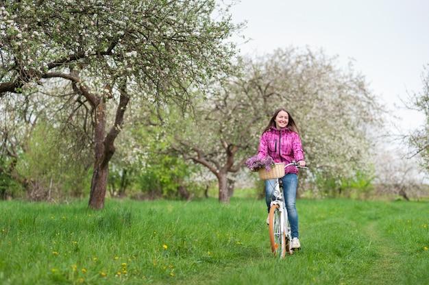 Donna che guida una bicicletta bianca d'annata nel giardino di primavera