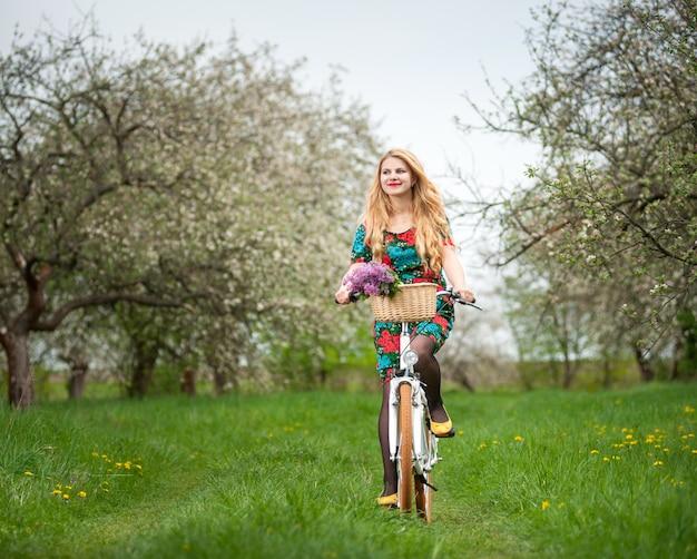 Donna che guida una bicicletta bianca della città nel giardino di primavera