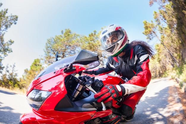 Donna che guida una moto su una strada di campagna
