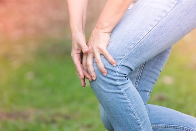Donna che ha dolore al ginocchio nel parco