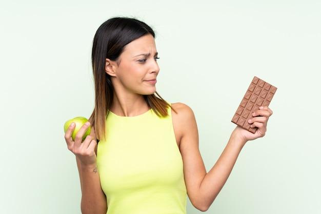 Donna che ha dubbi mentre prende una tavoletta di cioccolato in una mano e una mela nell'altra