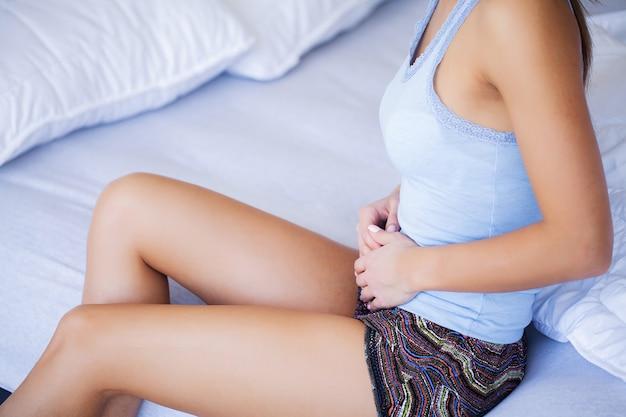 Donna che ha mal di stomaco doloroso, femmina che soffre di dolore addominale