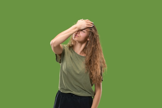 Donna che ha mal di testa. isolato sul verde.