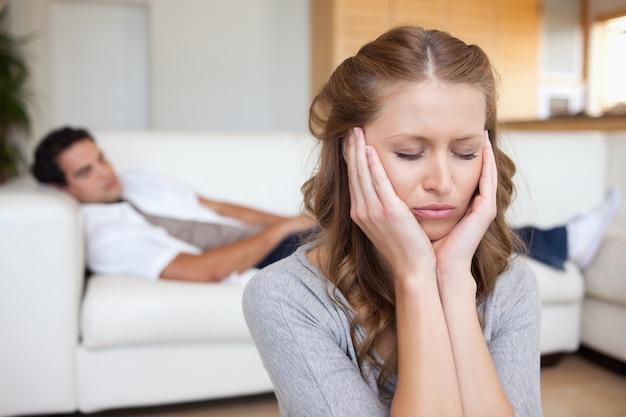Donna che ha mal di testa mentre uomo sdraiato sul divano dietro di lei