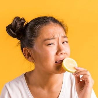 Donna che ha paura di mordere un limone