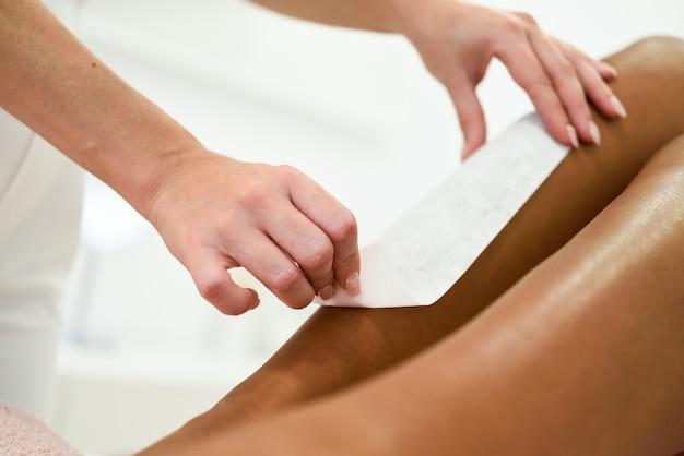 Donna che ha procedura di rimozione dei capelli sulla gamba che applica la striscia di cera