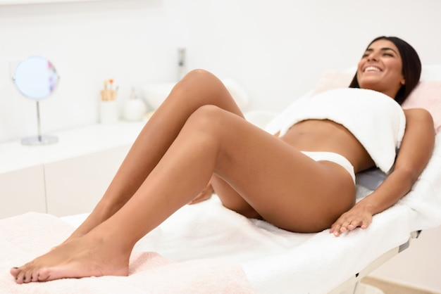 Donna che ha procedura di rimozione dei peli sulla gamba che applica la striscia di cera