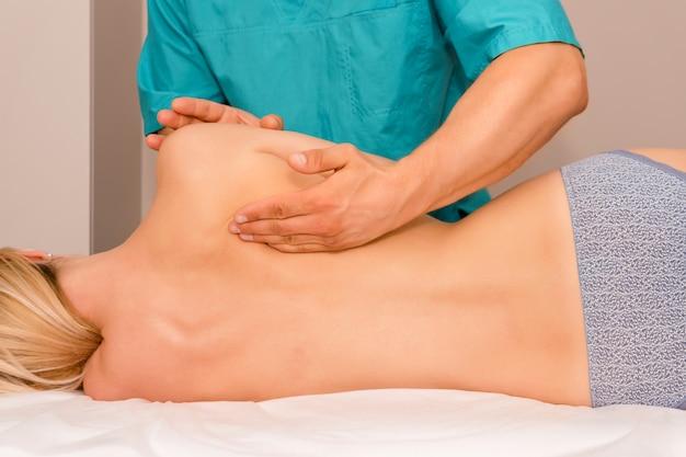 Donna che ha regolazione posteriore chiropratica.