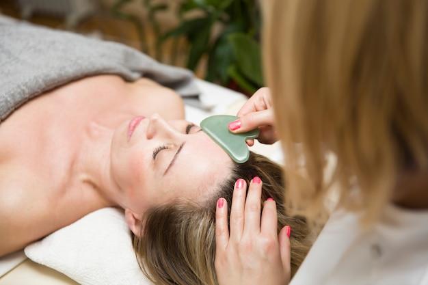 Donna che ha un massaggio facciale gua sha con massaggiatore di pietra di giada naturale