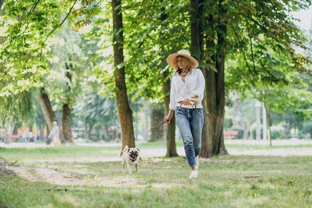 Donna che ha una passeggiata nel parco con il suo animale domestico del pug-dog