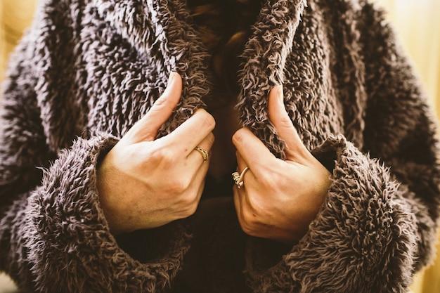 Donna che impacchetta in un cappotto lanuginoso durante l'inverno freddo.