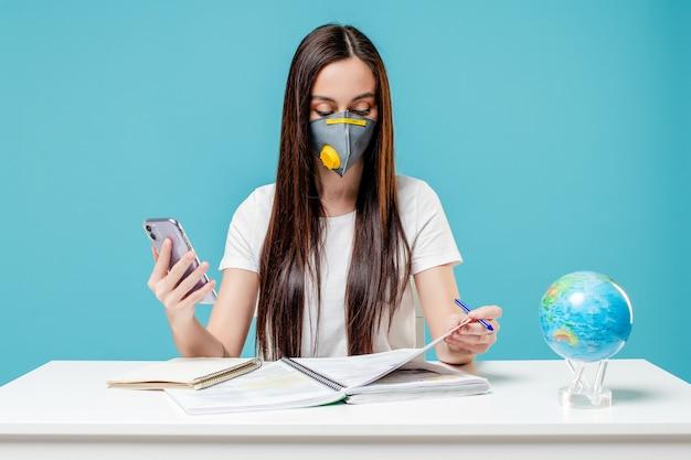 Donna che impara con il globo e il telefono del pianeta terra con i libri che indossano maschera