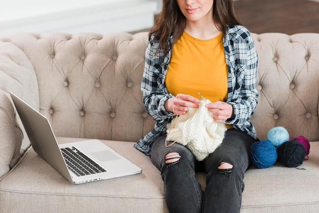 Donna che impara i corsi di maglieria online