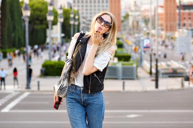 Donna che indossa abiti casual alla moda e invia un bacio d'aria