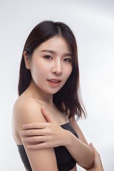 Donna che indossa camicette senza spalline nere gira la testa a destra e afferra il braccio.